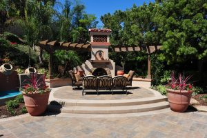 This Portofira estates home in Orange has a swimming pool renovation project that incorporated a new outdoor fireplace with a Spanish meets Santa Barbara theme. Red geraniums and Cordelyne flax, Spanish tiles and decorative arbor are included in this project. Bellgard interlocking pavers provide a pool safe decking while offering a lifetime warranty against cracking. Rogers Gardens furniture adds an element of sophistication and comfort. Outdoor speakers offer easy listening an integrate your iPod or iPad control.