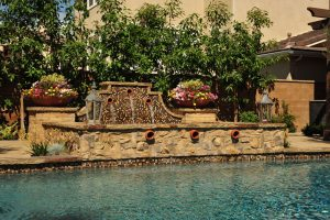 This Tustin Ranch residence has a beautiful raised spa and water feature as part of an overall swimming pool construction project in Orange County. As a premier pool builder in Orange County this design incorporated unique materials including glass waterline tile, natural stone, El Dorado Brick and Dakota flagstone pool coping. These decorative colorful plantings and pottery make this a relaxing retreat and soothing environment.