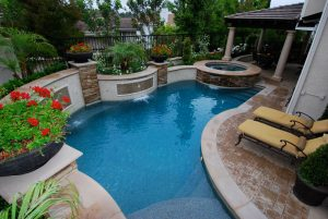 A swimming pool in Mission Viejo demonstrates how to maximize a small space. When Natural Touch was hired to design this backyard renovation the goals were clearly defined. Build a swimming pool, spa, sun deck, baja bench, outdoor room and cook center. Ordinarily the wish list of items is easily obtainable. The challenge with the Jenner residence was space. The solution gave them a backyard that not only delivered in terms of the design goals but also delivered in terms of features that were beyond what was expected. A raised bond beam wall created space for the pool and also gave a unique focal point by using glass tile and fountain sheer descents. An extra wide spa cap provided extra space for seating. A column for the outdoor pavilion is placed on the spa cap for architectural interest and also to provide extra deck space. Pottery accents introduce plant material while leaving room for a sun deck and lounge chairs. A sleeve for an umbrella creates shade at the baja bench during the heat of the summer.